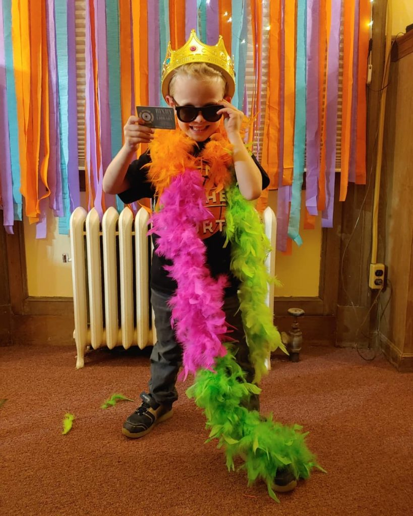 Young man with library card in sunglasses and feather boa smiling